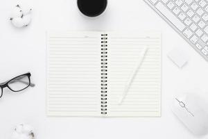 vista de cima da mesa de mesa de escritório mínima com páginas em branco do caderno aberto, teclado do computador, mouse, xícara de café em uma mesa branca com espaço de cópia, composição do local de trabalho de cor branca, disposição plana
