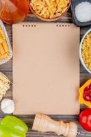vista de cima de diferentes macaronis como ziti rotini tagliatelle e outros com alho, manteiga derretida, sal, tomate, pimenta e ketchup em torno do bloco de notas sobre fundo de madeira com espaço de cópia foto