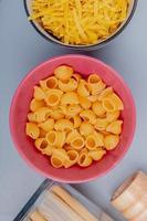 vista superior de diferentes tipos de macarrão em tigelas como pipe-rigate tagliatelle bucatini em fundo azul foto