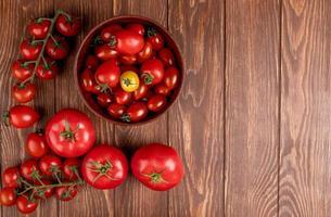 vista superior dos tomates em uma tigela com outros no lado esquerdo e fundo de madeira com espaço de cópia foto