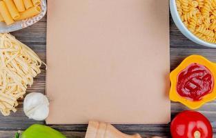 vista superior de diferentes macaronis como ziti rotini tagliatelle e outros com alho, tomate, pimenta e ketchup em torno de um bloco de notas sobre fundo de madeira com espaço de cópia