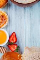 vista superior de morangos cortados pela metade com xarope de pêssego de aveia crocante e manteiga de cupcake em fundo de madeira com espaço de cópia foto