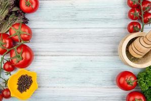 vista superior de vegetais como coentro de tomate com triturador de alho e pimenta preta nos lados esquerdo e direito e fundo de madeira com espaço de cópia