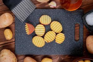 vista superior de fatias de batata babadas na tábua com manteiga de alho inteiras e sal no fundo de madeira foto