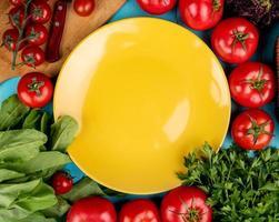 vista superior de vegetais como coentro de tomate, manjericão e espinafre com faca na tábua e prato vazio no fundo azul foto