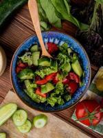 vista superior da salada de legumes com tomate cortado e fatiado, pepino, espinafre, manjericão, fundo de madeira foto