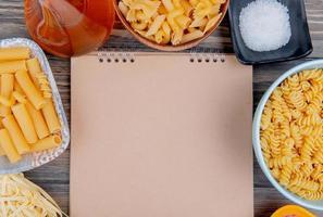 vista superior de diferentes macaronis como ziti rotini tagliatelle e outros com sal de manteiga derretida ao redor do bloco de notas em fundo de madeira com espaço de cópia foto