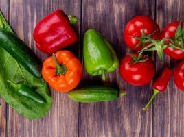 vista superior de vegetais como pepino, tomate e pimenta em fundo de madeira decorado com folhas foto