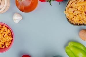 vista superior de diferentes tipos de macarrão como cavatappi pipe-rigate e outros com alho manteiga pimenta sal no fundo azul com espaço de cópia foto
