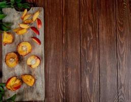 vista superior de pêssegos cortados e fatiados na tábua do lado esquerdo e fundo de madeira com espaço de cópia foto