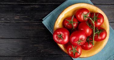vista superior dos tomates em uma tigela sobre um pano azul e fundo de madeira com espaço de cópia foto