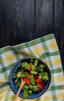 vista superior da salada de vegetais em pano xadrez e fundo de madeira com espaço de cópia foto