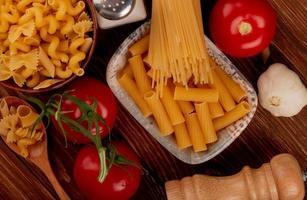 vista superior de macarrão ziti em uma tigela com espaguete e outros tipos em uma tigela e colher sal tomate alho no fundo de madeira foto