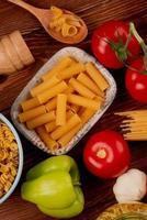 vista superior de macarrão ziti em uma tigela com tipos de espaguete e rotini em uma tigela e colher sal tomate alho pimenta no fundo de madeira foto