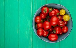 vista superior dos tomates na tigela do lado direito e fundo verde com espaço de cópia