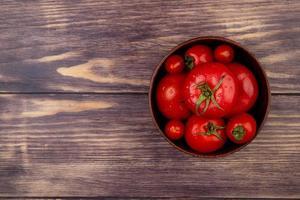 vista superior dos tomates na tigela do lado direito e fundo de madeira com espaço de cópia