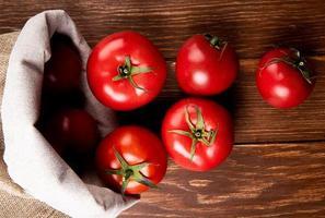 vista de cima de tomates derramando do saco no fundo de madeira foto