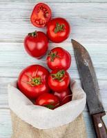 vista superior do tomate derramando do saco e da faca no fundo de madeira foto