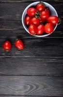vista superior dos tomates em uma tigela sobre fundo de madeira com espaço de cópia