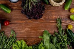 vista de cima de vegetais como pepino, tomate, manjericão, hortelã, alface, espinafre com sal de pimenta do reino em fundo de madeira foto