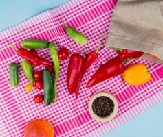 vista de cima de pimentas derramando do saco com pepinos, tomates e sementes de pimenta preta com óleo derretido em um pano xadrez e fundo azul foto