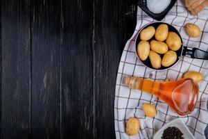 vista superior de batatas na panela com sal manteiga derretida sementes de pimenta preta em pano xadrez e fundo de madeira com espaço de cópia