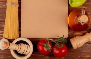vista de cima de macarrão espaguete com sementes de pimenta-do-reino, tomates, pimenta, sal e manteiga derretida em torno do bloco de notas no fundo de madeira com espaço de cópia foto