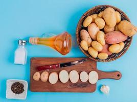 vista de cima das fatias de batata e da faca na tábua de cortar com as inteiras na cesta, manteiga, sal e pimenta do reino e alho no fundo azul foto
