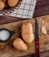 vista superior de batatas com faca de casca e sal na tábua com outras na cesta em pano com fundo de madeira foto
