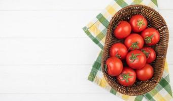 vista superior de tomates em uma cesta em um pano no lado direito e fundo branco com espaço de cópia foto