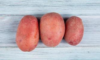 vista superior de batatas vermelhas em fundo de madeira foto