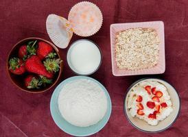 vista de cima de morangos em uma tigela com farinha de queijo cottage leite e aveia no fundo de pano de bordo
