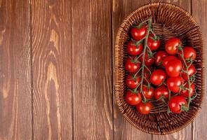 vista superior dos tomates na cesta no lado direito e fundo de madeira com espaço de cópia