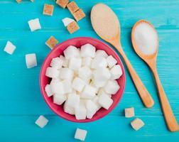 vista superior de cubos de açúcar em uma tigela rosa e colheres de madeira com açúcar no fundo azul foto