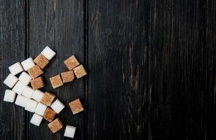 vista superior de cubos de açúcar mascavo e branco espalhados no fundo escuro de madeira com espaço de cópia foto
