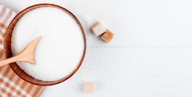 vista superior do açúcar branco em uma tigela de madeira com uma colher e cubos de açúcar no fundo branco com espaço de cópia foto