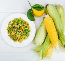 vista superior da salada de milho e espigas de milho com limão no fundo de madeira foto