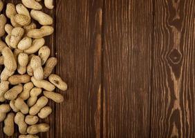 vista superior de amendoim em fundo de madeira com espaço de cópia foto