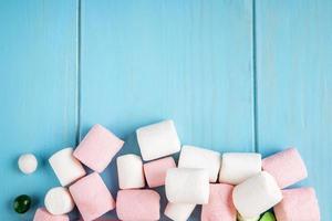 vista superior do marshmallow na parte inferior em fundo azul de madeira com espaço de cópia foto