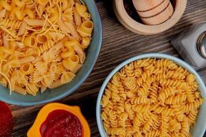 vista superior de macaronis como rotini e outros em tigelas com ketchup sal pimenta preta em fundo de madeira foto