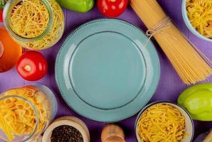 vista superior de macaronis como espaguete vermicelli tagliatelle e outros com tomate pimenta preta, manteiga e prato no fundo roxo foto