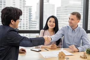 casal apertando as mãos como acordo bem-sucedido no contrato de transação da casa com o corretor.