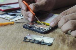 reparo de smartphone por um técnico profissional em uma mesa. foto