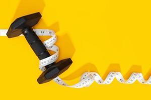 halteres e fita métrica em fundo amarelo