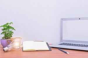 laptop e outros objetos na mesa foto