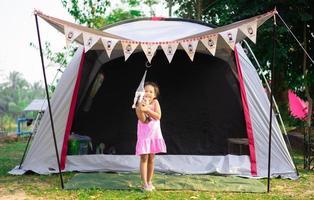 garotinha asiática em frente a uma barraca enquanto vai acampar
