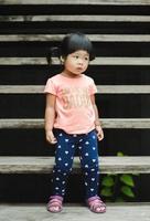 menina fica na escada de madeira