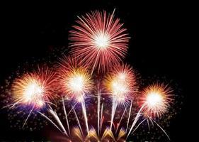 abstrato colorido feriado fogos de artifício celebração de fundo na véspera de ano novo um festival de alegria exibição de fogos de artifício no céu noturno foto