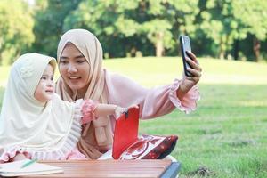 mãe muçulmana e filha tirando uma selfie feliz no parque foto