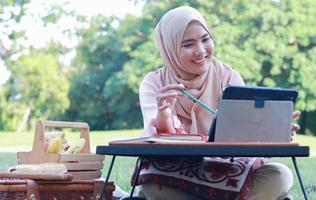 linda garota muçulmana sentada alegremente no parque. mulher muçulmana sorrindo no gramado do jardim. conceito de estilo de vida de uma mulher moderna confiante